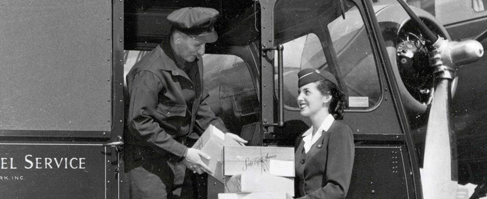 Chauffeur-livreur UPS remettant des colis à une hôtesse de l'air devant un avion